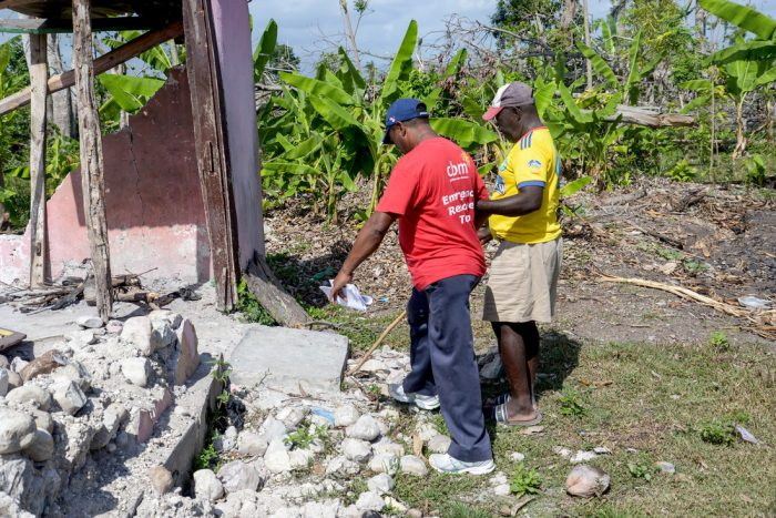 René, who is blind, with a CBM aid worker visiting the remains of his house, destroyed in the hurricane.