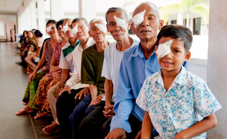 Patients with eye patches wait in an open-sided verandah