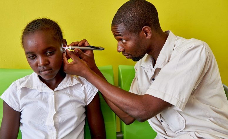 Hearing technician examines girl's ear