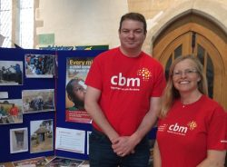 CBM staff and volunteer with an information display in a church