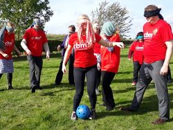 Staff wearing CBM t-shirts and blindfolds play football