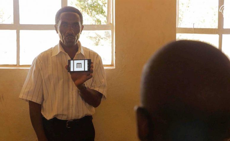 Teacher holds up a phone showing letter E as part of a visual acuity test