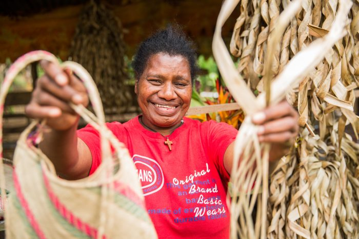 Harriette is 48 years old and lives in Vanuatu. She is deaf and has had limited access to education. She is holding a bag she has weaved herself.