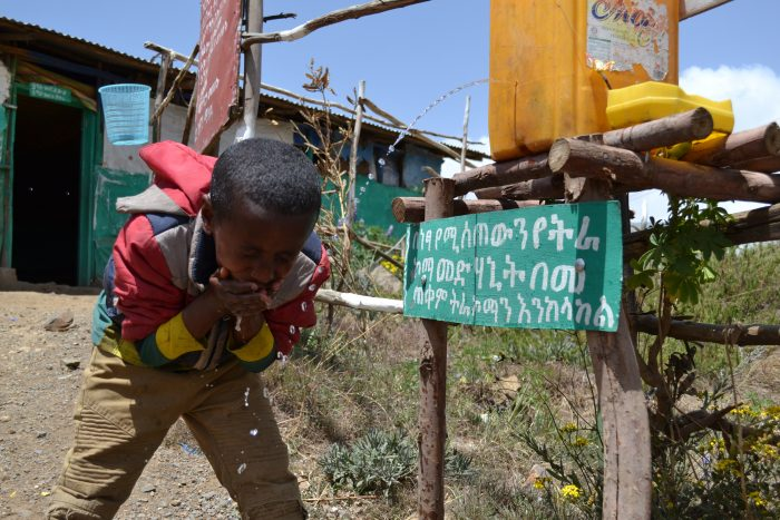 Faud (aged 8) washing his face at the wash station