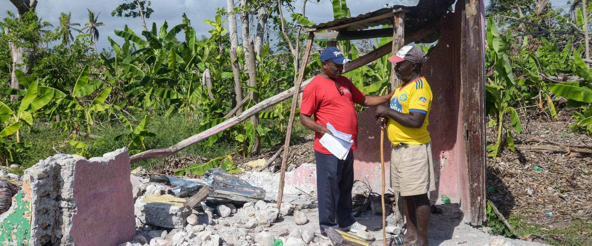 Rene showing CBM Community Worker what is left of his house in Torbeck, Haiti, after Hurricane Matthew made landfall.