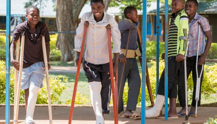 Twizerimana (18 years, male) is smiling and walking with other patients at the Gahini hospital, in Rwanda, after receiving surgery on his right knee.