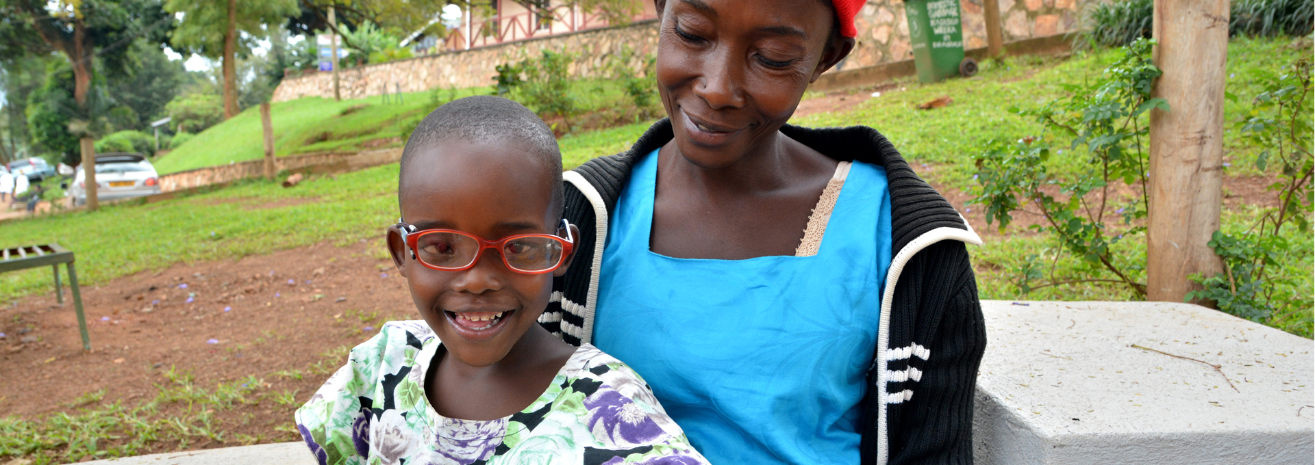 Shakulu sitting with his mother, Zaitun, wearing glasses and smiling after successful cataract surgery.