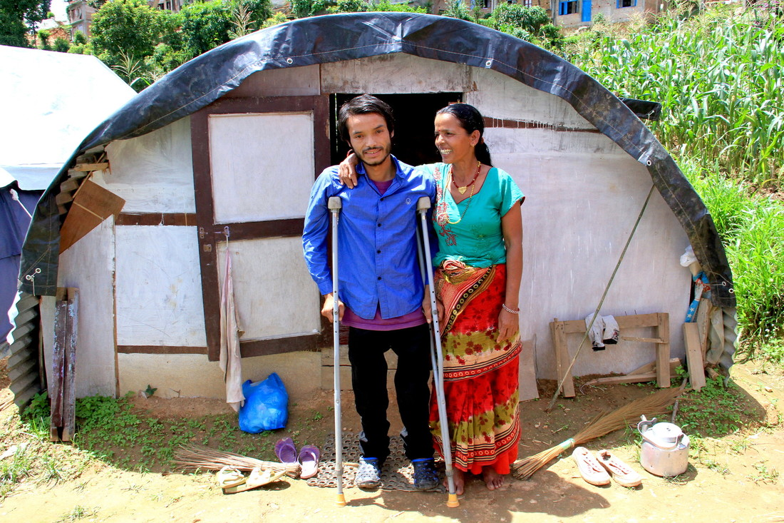 Rajesh, 27, with crutches, stands in front of corrugated iron shelter with his mother, who is smiling at him