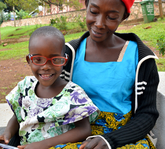 Shakulu wearing glasses, sat with his mother Zaitun. Both smiling after successful cataract surgery.