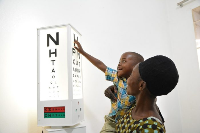 Shakulu pointing and smiling as he can read the letters on the eye test.