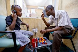 Edson (6) is doing a hearing test with Patson Sakala, hearing instruments specialist at Beit CURE Hospital in Zambia.