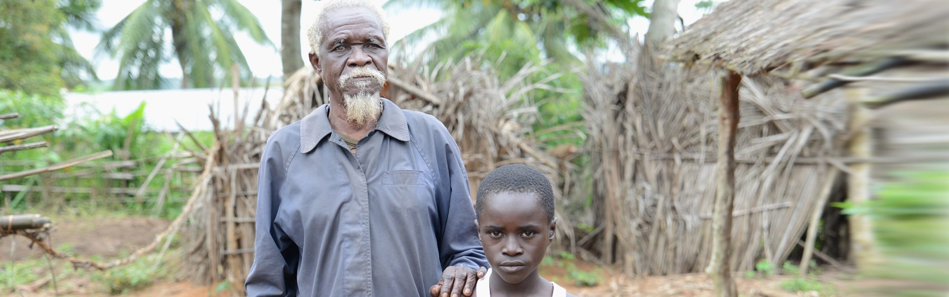 Albert and his grandson Marceil, standing outside his hut. Albert has been blind for 10 years because of River Blindness.