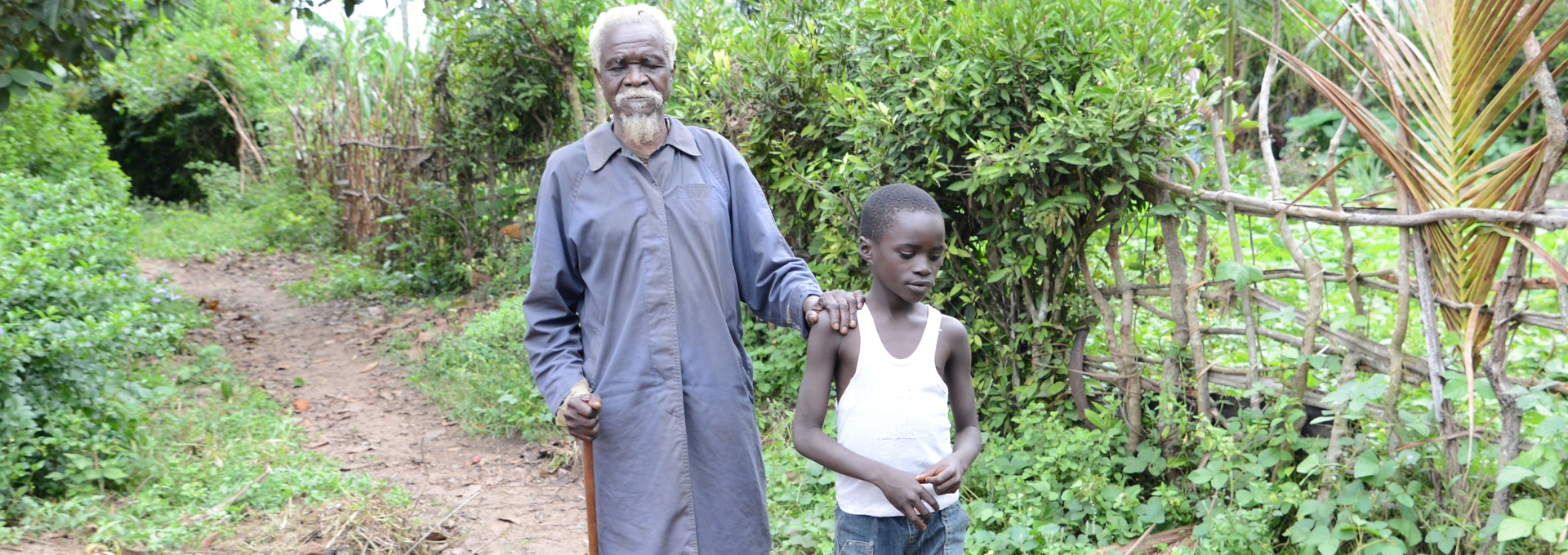 Albert being led along a path by his grandson Marceil. Albert has been blind for 10 years because of River Blindness.