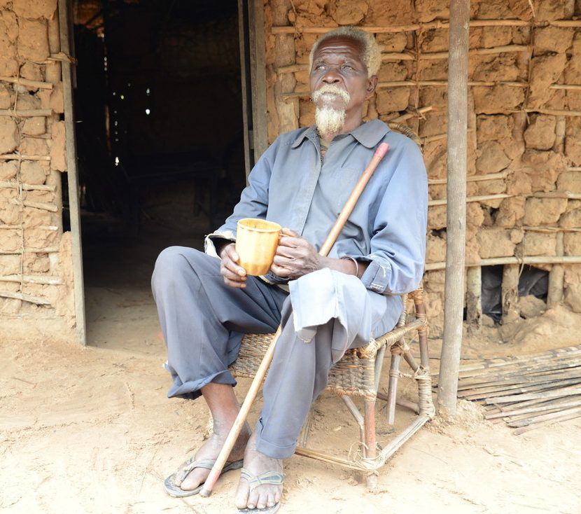 Albert sitting outside his home, holding his cane and a cup.