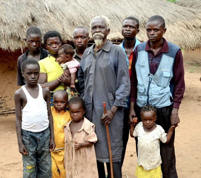 Albert and his family standing outside their mud hut