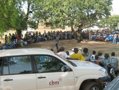 community meeting in rural area, vehicle withCBM logo