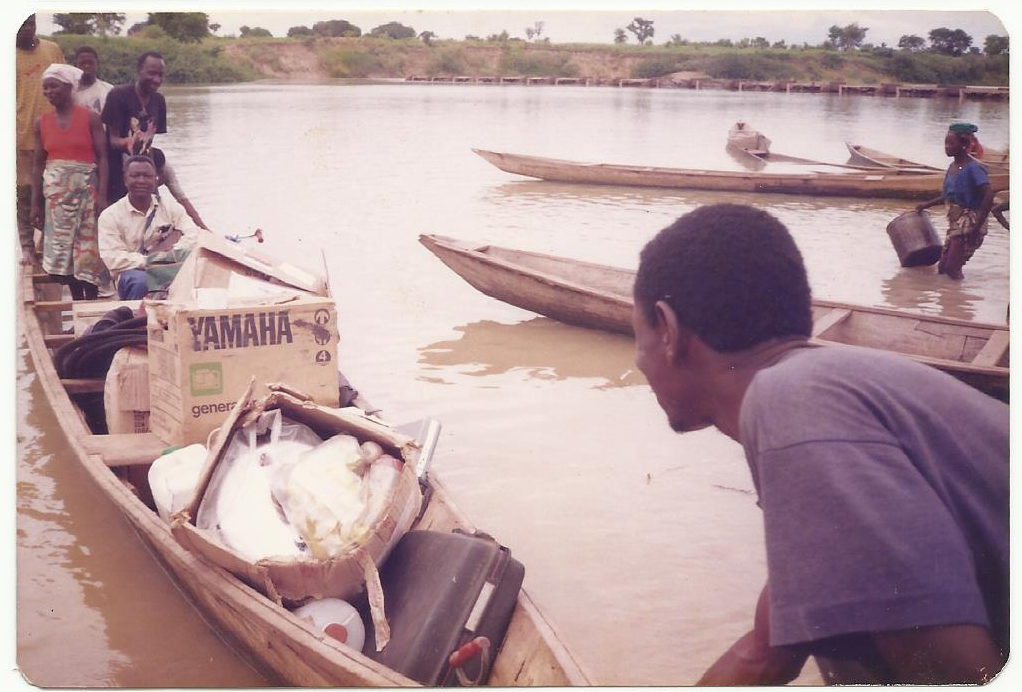 two nurses setting off in a small wooden boat packed with boxes of supplies
