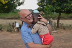 Dave cuddling Gnasher who has cerebral palsy in Zimbabwe in 2017.