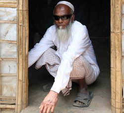 Abul crouching in his makeshift tent at the refugee camp in Bangladesh.