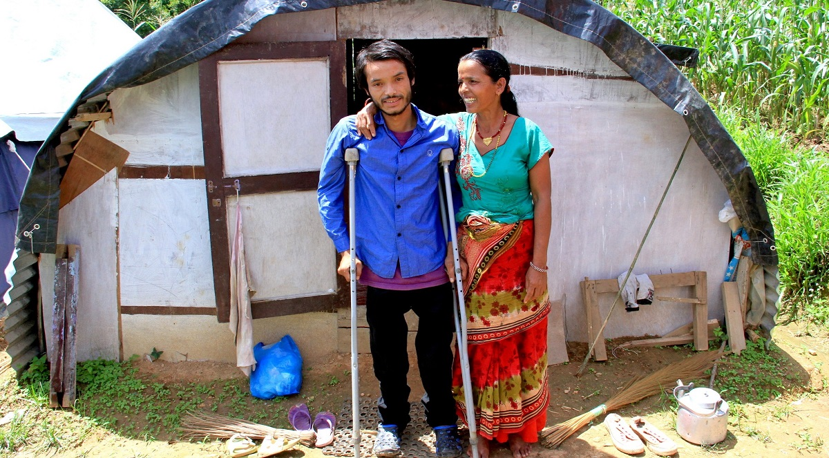 Rajesh, on crutches, with his mother outside the shelter built by CBM's partner after the Nepal earthquake