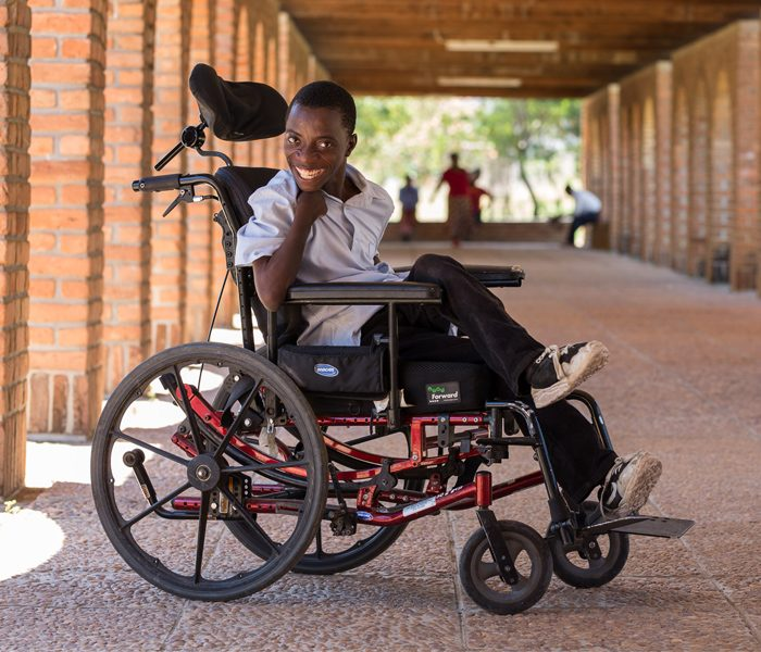Prince from Malawi can go to school now he has been provided a wheelchair by CBM.
