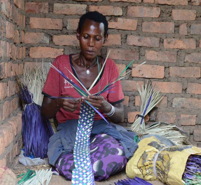 Prisca sat on the floor of her home, weaving a mat.