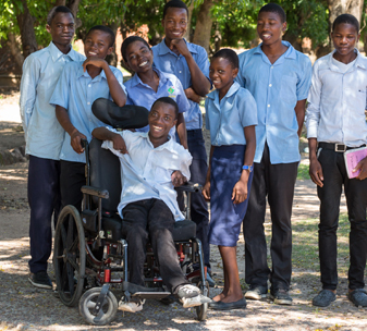 Prince from Malawi with his school friends. He can get to and from school now CBM has provided a wheelchair for him.