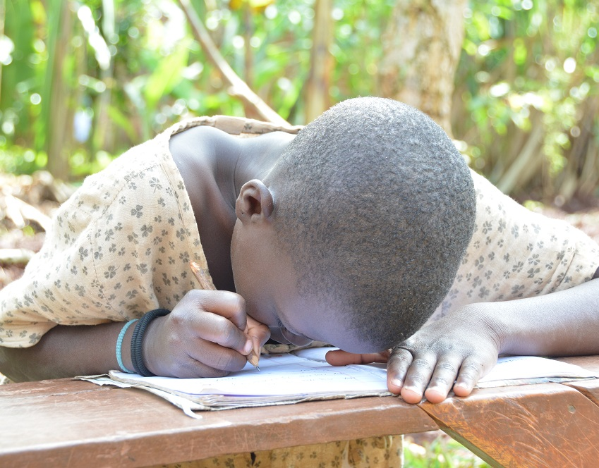 Allen before intervention at home. Please refer to respective story for more.information Allen– 9 years old –was born with bilateral cataracts. She lives in a village west of Uganda's capital Allen has to place her head close to the book to be able to write. She still writes randomly.