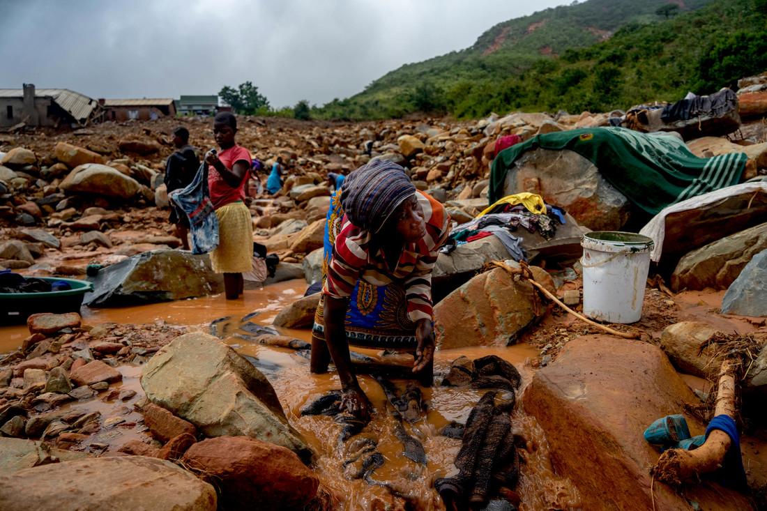 Woman washes belongings in the mud (ZINYANGE AUNTONY / AFP)