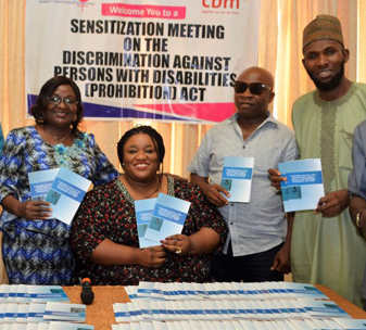 Irene Patrick-Ogbogu DRAC Executive Director (centre), plus DRAC members, gather to launch the Simplified Version of Nigeria's new disability legislation.