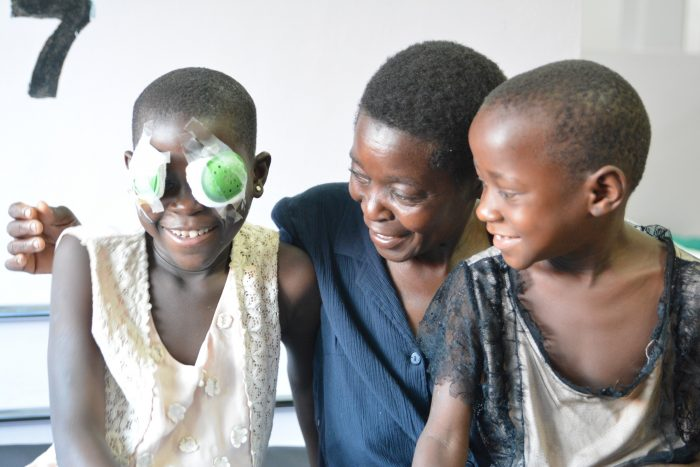 Allen with bandages on her eyes after successful cataract surgery. Sitting and smiling with her mother and brother.