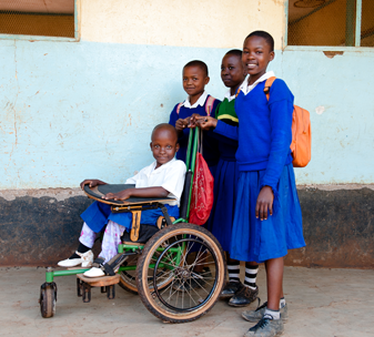 Nine-year-old Elisabeth was born with spina bifida and used to struggle to get to school – but since receiving a wheelchair from CBM's partner in Tanzania, her sister can push her to school.