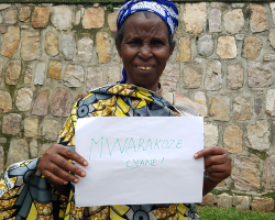 Salome holds a sign which says 'Thank You' in Kinyarwanda