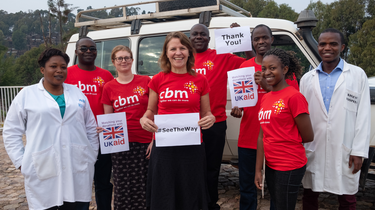 CBM staff and partners holding banners with 'See the Way', 'Thank You' and the UK Aid Match logo on.