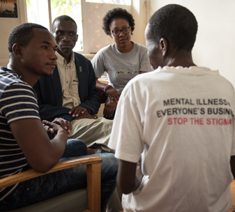 Group of people talking. Back of Tshirt reads Mental Illness, Everyone's Business, Stop the Stigma.