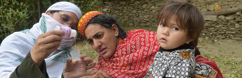 Community health worker distributing medicine to prevent trachoma in Pakistan