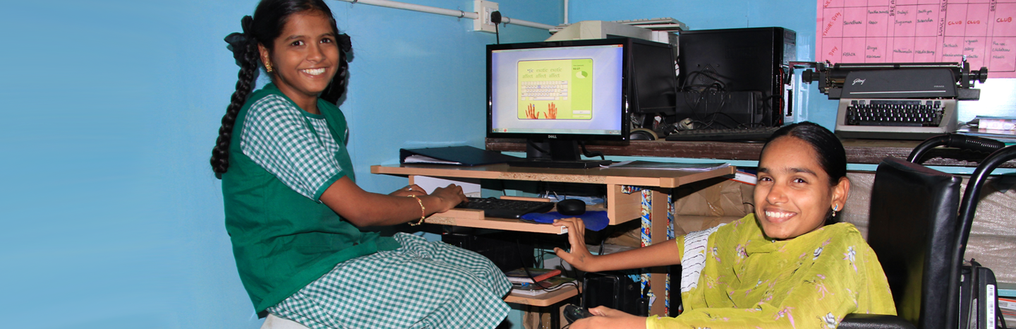 A lady in a wheelchair teaching a young girl IT skills.