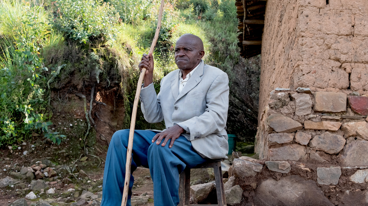Jean-Baptiste sitting outside his home, holding his walking stick