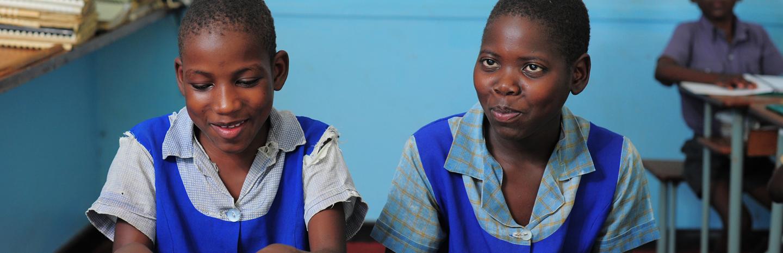 Two schoolgirls in Zimbabwe smiling