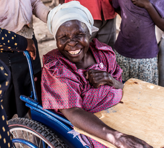 Nusula Amalemo takes a ride in a new wheelchair provided by CBM UK, at her home in Namutumba, Uganda.