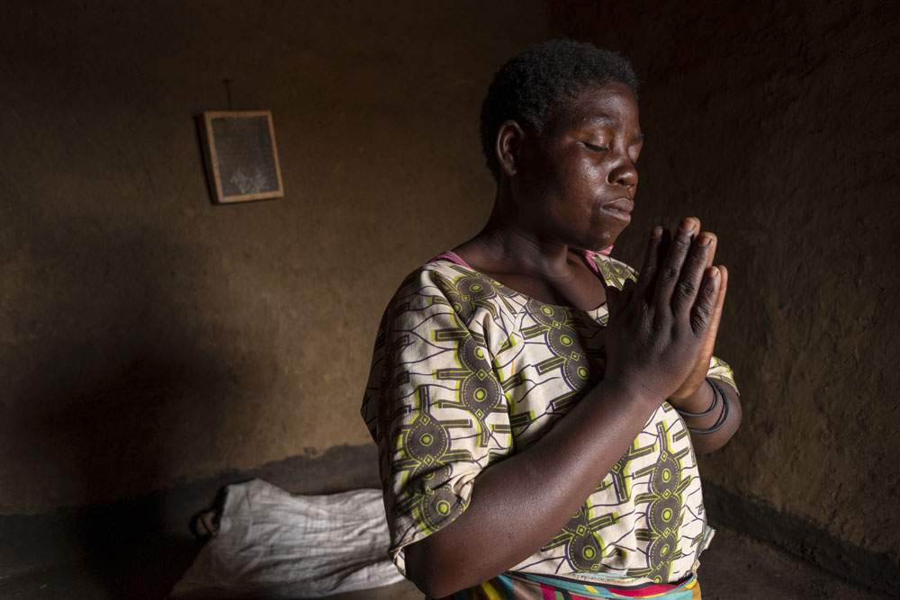 Njiruzalo praying in her home a village on the outskirts of Nathanje, Malawi