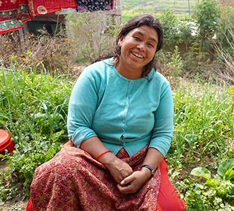 Bimala sitting in her garden smiling
