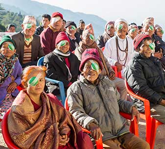 Group of elderly patients smiling after successful cataract surgery at a mobile surgical camp in Nepal, supported by CBM.
