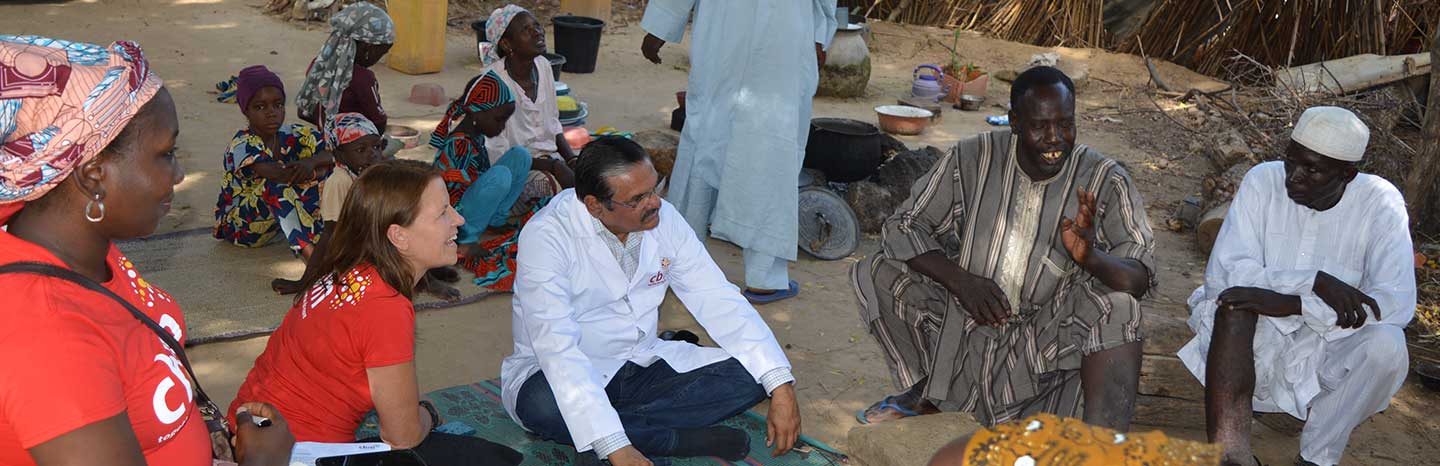 Group of people sit together on the floor. One man is living with Lymphatic filariasis