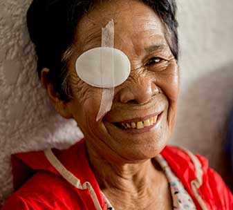 A patient smiles after successful cataract surgery at CBM's partner hospital in the Philippines.