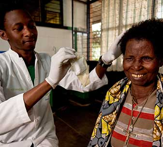 Salome from Rwanda is smiling as she has her eye bandages removed after cataract surgery.
