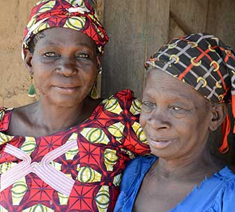 Mairige (70, right) with her sister Hauwa (55, left). Mairige lives in rural Nigeria and lost her sight due to river blindness.