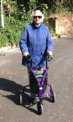 Margaret out walking, using her three-wheeled walker