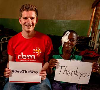 L-R: CBM staff member Jonny holding a #SeeTheWay sign and Jabes holding a Thank You sign, after Jabes has had successful surgery at CBM's partner hospital in Malawi.