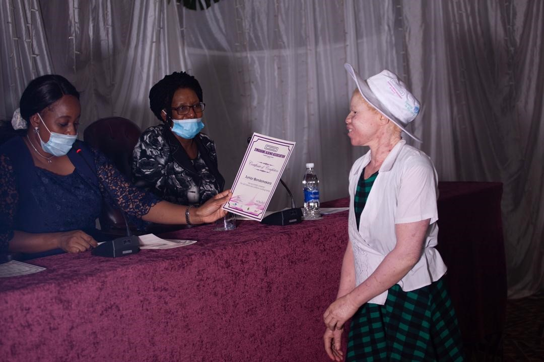 Girl with albinism being presented with certificates of completion in self-esteem and confidence building